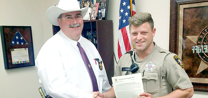 Sheriff Greg Capers shakes hands with Deputy Sheriff Cody Hardy as he holds a letter of commendation to honor the deputy for his selfless act of service for a family in need when he responded to a call at the end of January in Shepherd.